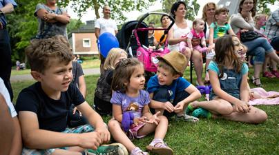 Kinder sitzen auf der Wiese im Kinderdorf und freuen sich auf den Flohmarkt.